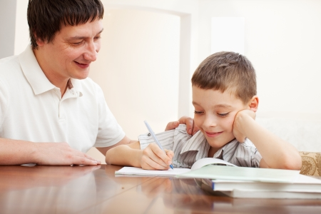 helps: Father helping son do homework. Parent helps his child Stock Photo