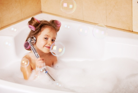 Little girl  in curlers in the bathtub. Girl washes in the bathroom photo