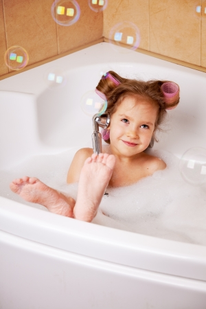 Little girl  in curlers in the bathtub. Girl washes in the bathroom