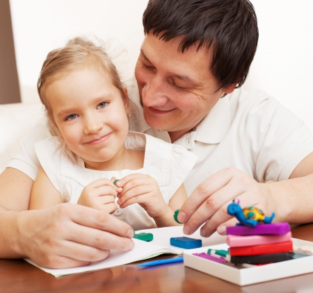 Father play with child at home. Family molded from clay toys.  Stock Photo - 17283430