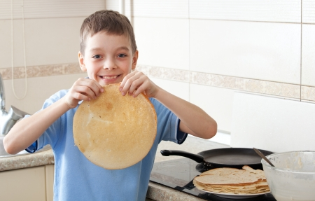 Child bakes pancakes in the kitchen. Boy cooking breakfast photo