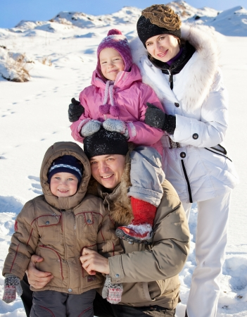 Family with children on snow in winter photo