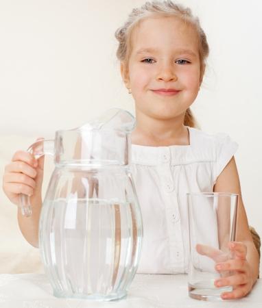 purified water: Ni�o con el vidrio de agua lanzador. Ni�a de agua potable en el hogar