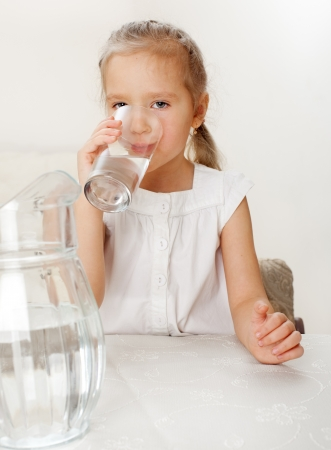 Child with glass pitcher water. Little girl drinking water at home Stock Photo - 17534505