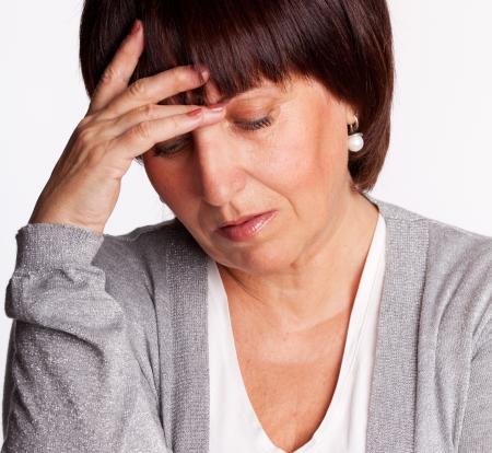 Sadness mature woman. Isolated on gray photo