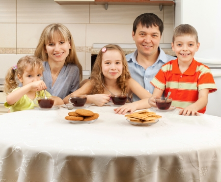 large house: Happy family at breakfast in the kitchen Stock Photo