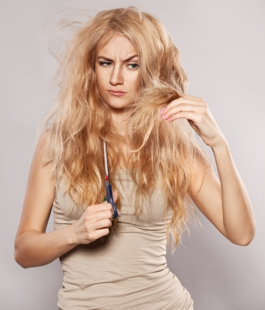 Young woman looking at split ends. Damaged long hair photo