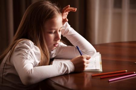 elementary age girl: Child doing homework. Sad girl writing, reeding Stock Photo