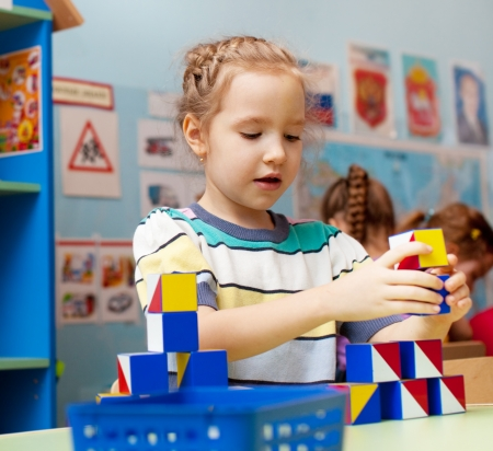 Niño en jardín de infantes. Los niños en la guardería. Niña jugando en la escuela infantil. Juego