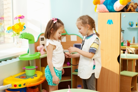 doctor toys: Child in kindergarten. Kids in nursery school. Girl playing at infant school