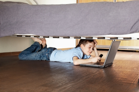 Child with laptop and phone under the bed. Boy playing computer photo