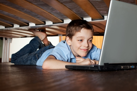 Child playing laptop under the bed. Computer Addiction photo