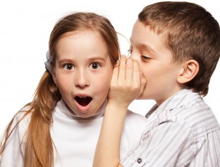 whispering: Boy whispers girl in the ear secret. Childrens gossip