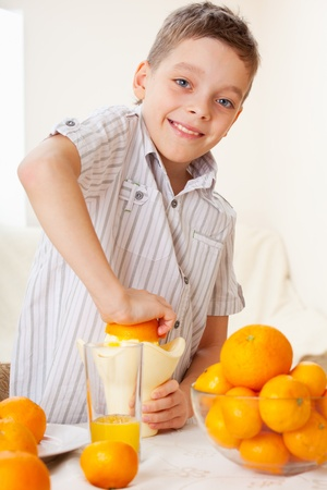 boys only: Child with oranges. Happy boy squeezed orange juice.  Stock Photo