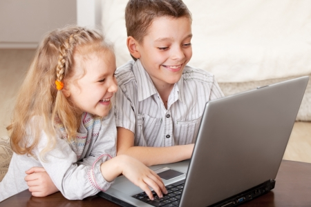 Children with laptop indoors. Happy kids playing computer at home. Stock Photo