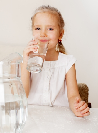 purified water: Ni�o con agua de jarra de cristal. Ni�a de agua potable en el hogar Foto de archivo