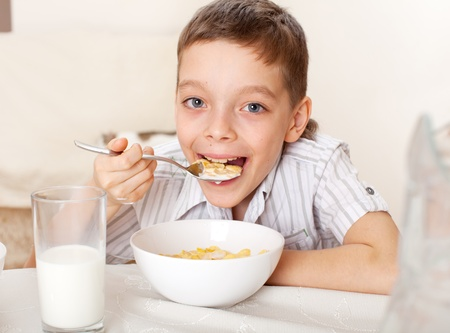 replenishment: Child eat breakfast. Boy eating cereals with milk