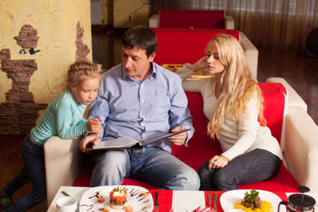 Family chooses the menu in the cafe. Mother, Father and child in cafe photo