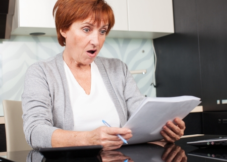 Surprised businesswoman with document. Elderly woman sorting through her old receipts at home. Stock Photo