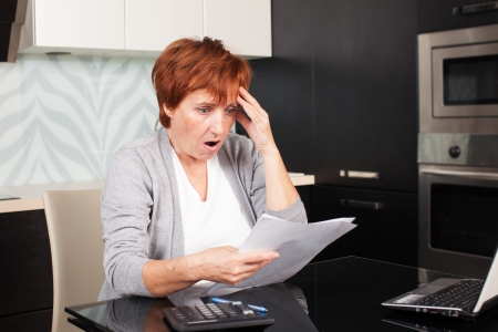 banking document: Elderly woman sorting through her old receipts at home. Sad businesswoman with document