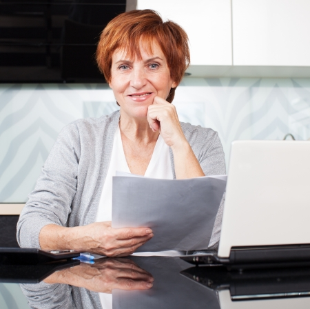 documentation: Happy businesswoman with documentation at home Stock Photo