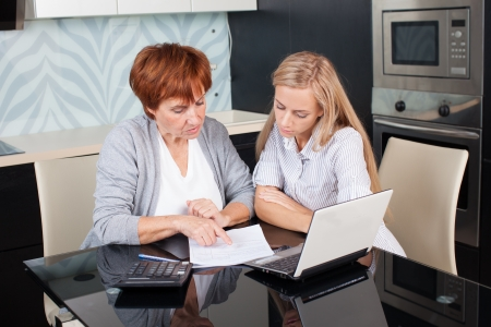 Two women discussing documents at home. Consultant with woman