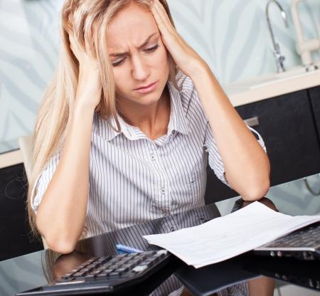 woman issues: Mujer triste que mira a la cuenta. Hembra que trabaja en casa