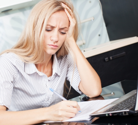 Female working at home. Sad woman looks at the bill. Stock Photo