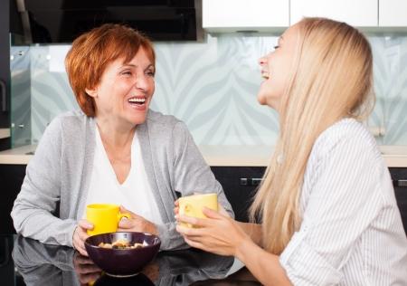 gossip: Moeder en daudhter praten over de keuken. Vrouwen thuis Stockfoto