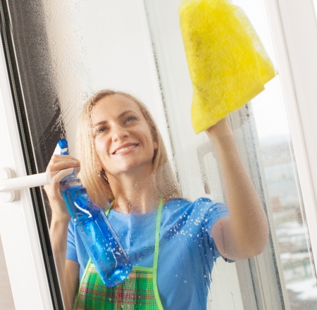 window cleaning: Woman washing window. Housewife cleaning window at home. Housework
