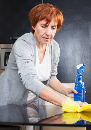 Woman cleaning the kitchen. Adult woman washing house photo