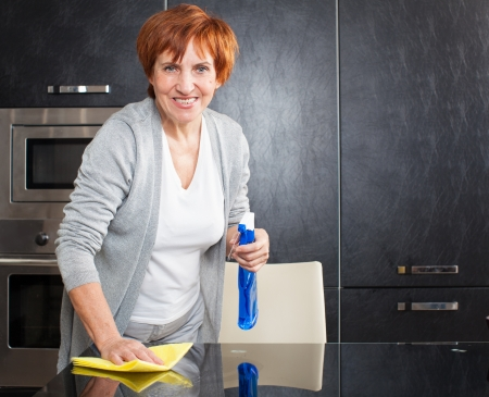 Woman cleaning the kitchen. Adult woman washing glass table photo