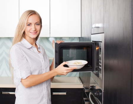 Young woman warms up food in the microwave