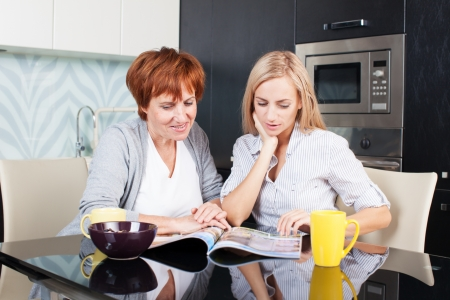 adult magazines: Mother and daughter read magazine at home. Happy women on the kitchen Stock Photo
