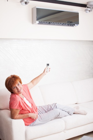 hot climate: Woman holding a remote control air conditioner at home. Happy mature woman on sofa