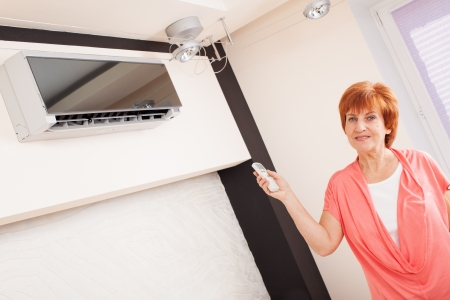 air show: Woman holding a remote control air conditioner at home. Happy mature woman on sofa