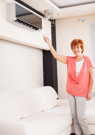 cooling system: Woman holding a remote control air conditioner at home. Happy mature woman on sofa