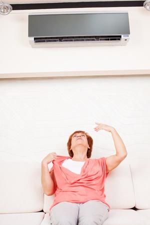 aire acondicionado: Mujer escapa del calor en el aire acondicionado en casa. Mujer madura feliz en el sof?