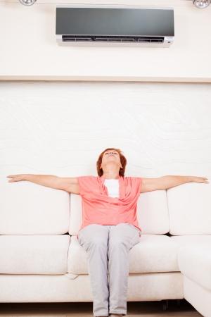 h�nde in der luft: Frau fl�chtet vor der Hitze unter der Klimaanlage zu Hause. Gl�cklich reife Frau auf dem Sofa Lizenzfreie Bilder