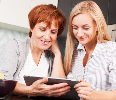 Mother and daughter looking in tablet pc photo