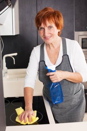 Woman cleaning the kitchen. Adult woman washing stove photo