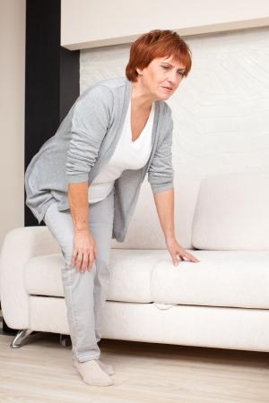 artritis: Mujer adulta tiene dolor en la rodilla. Mujer madura en casa