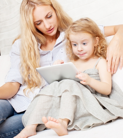 Woman and little child with tablet computer photo