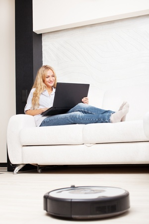 vacuum: Female lying on the sofa, and the robot vacuum cleaner cleans Stock Photo