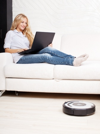 Female lying on the sofa, and the robot vacuum cleaner cleans Stock Photo
