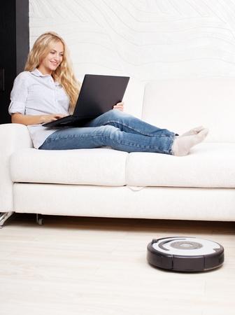 personal de limpieza: Mujer tumbada en el sof�, y la aspiradora robot limpia