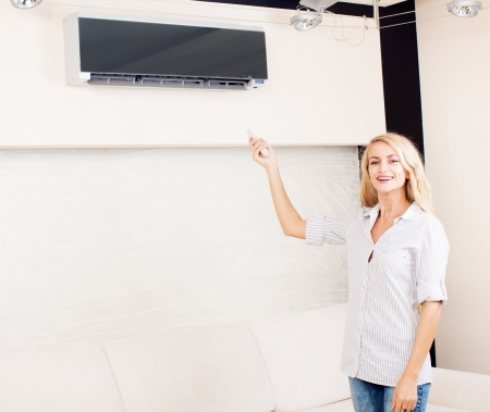 Female holding a remote control air conditioner at home photo