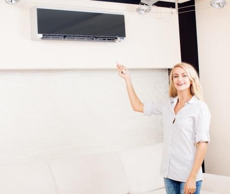aire acondicionado: Mujer sosteniendo un control remoto de aire acondicionado de control en el hogar Foto de archivo