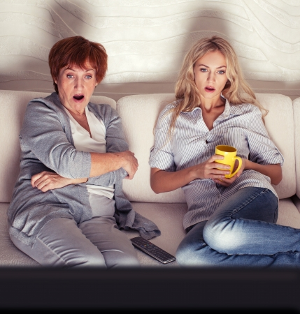 thriller: Mother with adult daughter watching television  Women looking film thriller