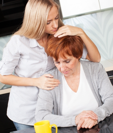 senior adult woman: Daughter soothes sad mother. Young woman calm mature woman